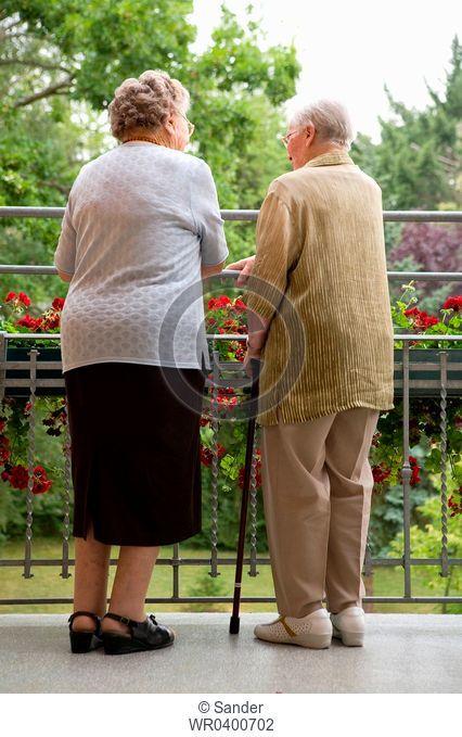 Two senior women standing on balcony