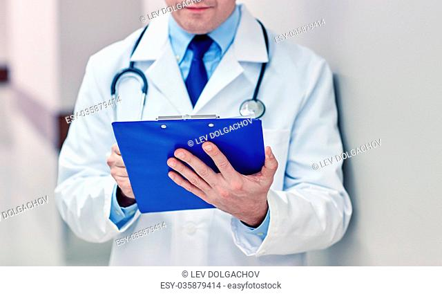 medicine, healthcare, profession and people concept - close up of male doctor with clipboard at hospital