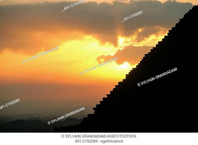 EGYPT.CAIRO.GIZEH.THE CHEOPS PYRAMID BACKLIGHTED AT SUNRISE