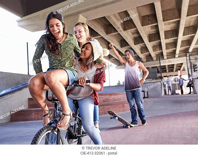 Playful teenage friends riding BMX bicycle and skateboarding at skate park