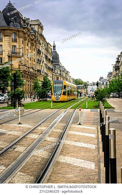Tram running down the center of Cours Jean Baptiste Langlet in Reims France