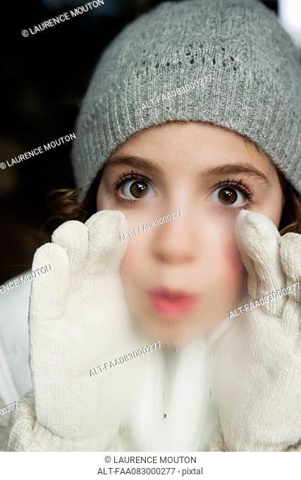 Girl breathing on window, dressed in winter clothes