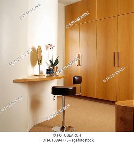 Leather stool at shelf in modern bedroom with fitted wardrobe