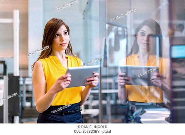 Young woman in factory, holding digital tablet