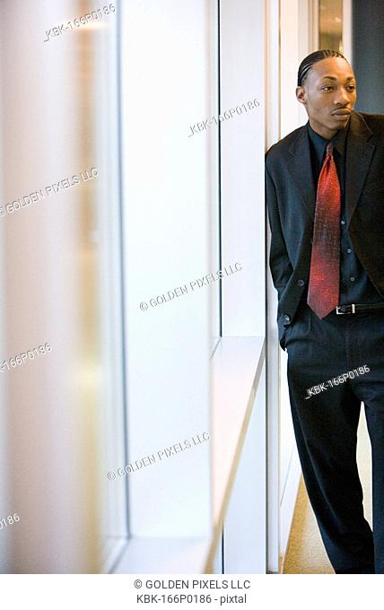 Businessman standing and leaning against a window