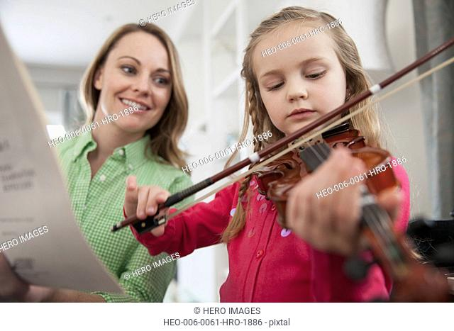 Mother holding music sheet while daughter practices violin at home