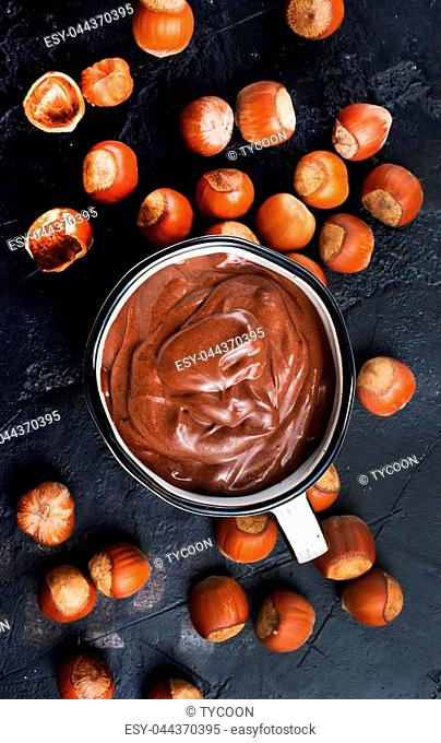 Homemade hazelnut spread or hot chocolate in cup with nuts and chocolate bar