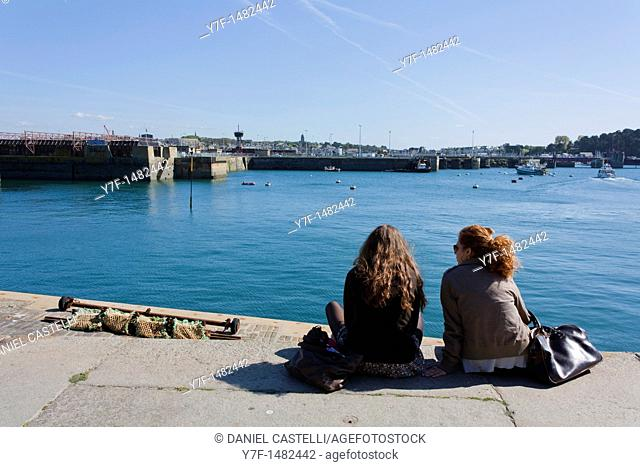 Two young pretty girl watching boat on harbour