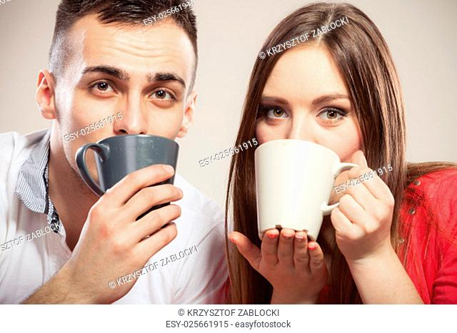 close up of young couple drinking coffee mugs holding on gray background