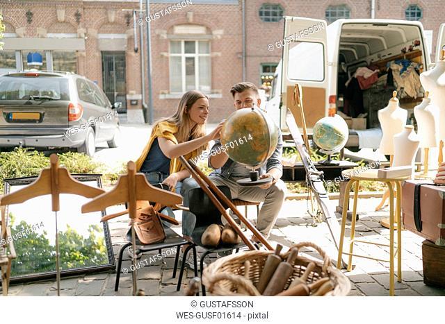 Belgium, Tongeren, young couple examining globe on an antique flea market