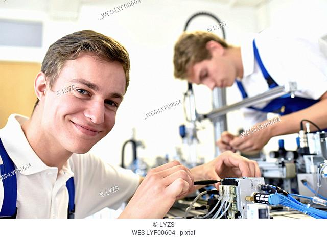 Portrait of smiling student working with pneumatics component parts