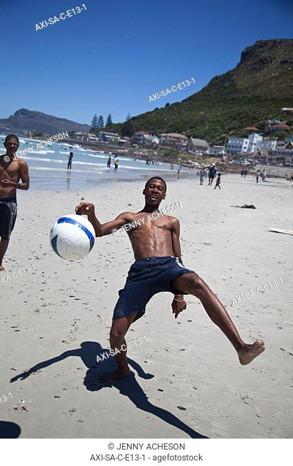 Local boys playing football on beach, Muizenberg, Cape Town, South Africa