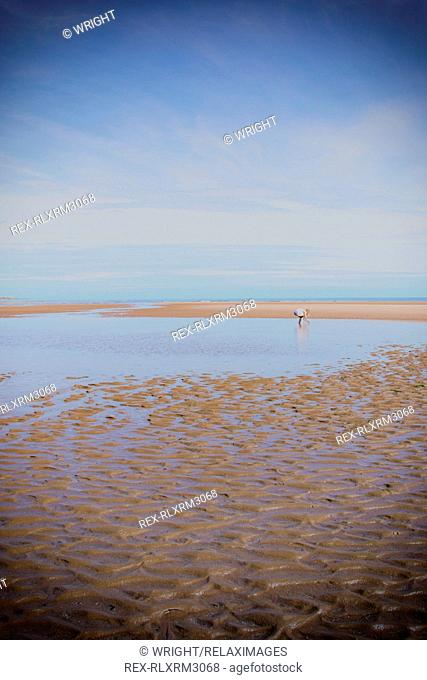 Mid distance of teenage girl on beach against sky