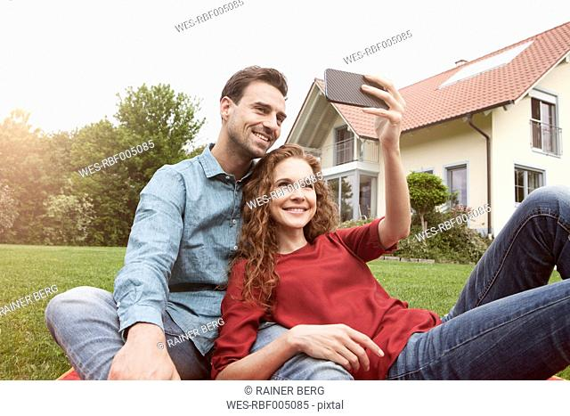 Smiling couple sitting in garden taking a selfie
