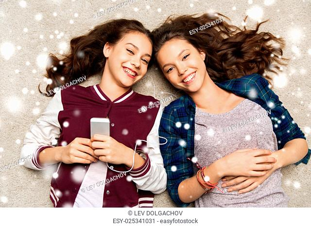 people, winter, christmas and technology concept - happy smiling pretty teenage girls or friends with smartphones and earphones listening to music over snow