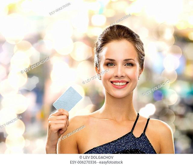 shopping, wealth, money, luxury and people concept - smiling woman in evening dress holding credit card over holidays lights background