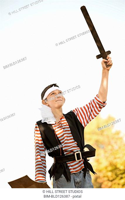 Caucasian boy in pirate costume holding sword
