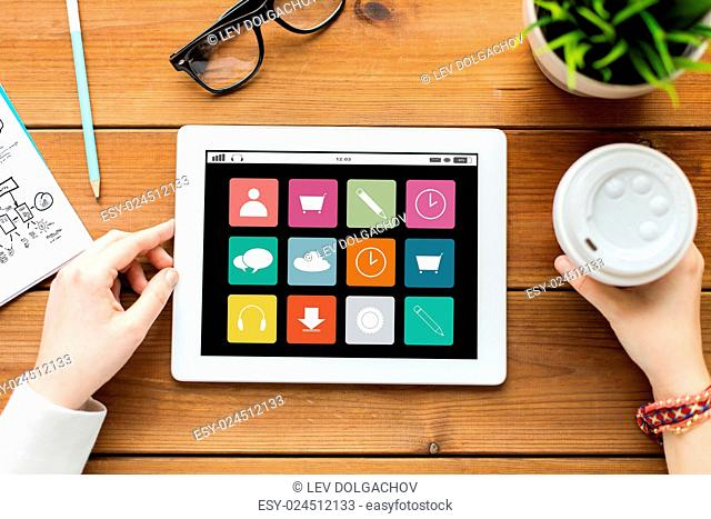 business, education, technology, people and multimedia concept - close up of woman with menu icons on tablet pc computer screen and coffee on wooden table