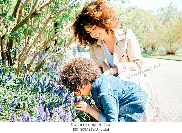 Mother and daughter bending over smelling flowers