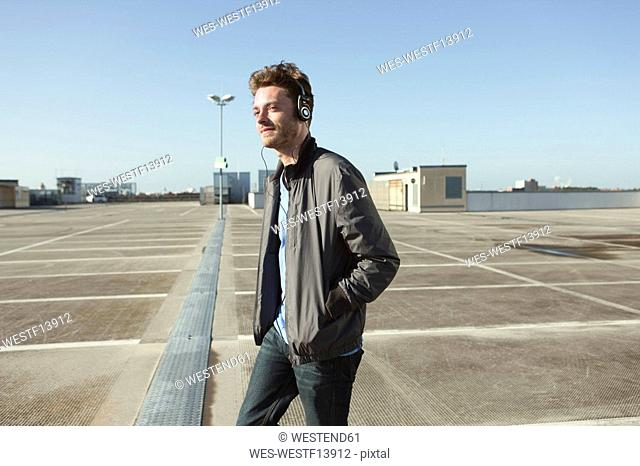 Germany, Berlin, Young man standing in car park listening to headphones