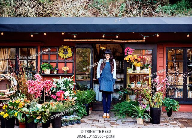 Mixed race florist standing outside shop