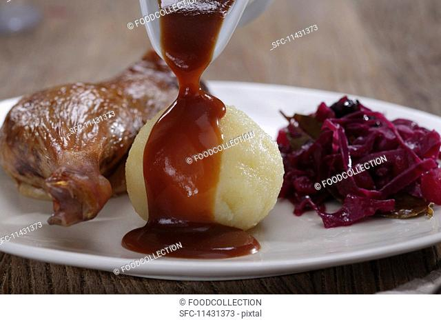 Leg of goose with red cabbage and dumpling with demi glace being poured over the dumpling