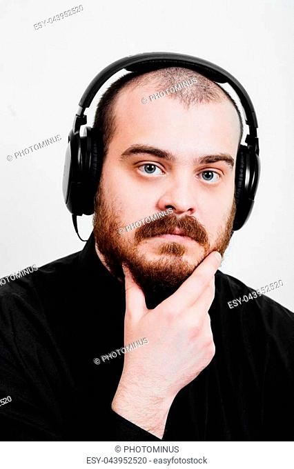 Portrait of a red-bearded, balding male brutal. White isolated background. A man in a black shirt pants. Headphones listening to music. keeps his chin