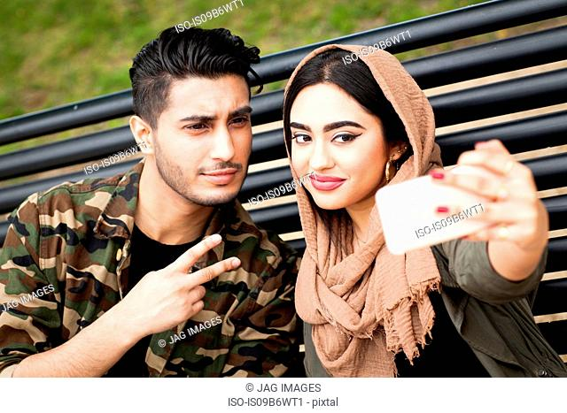 Young man and woman, sitting on park bench, taking selfie with smartphone