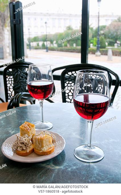 Spanish aperitif: two glasses of rose wine with tapa of Spanish omelet and gulas. Oriente Square, Madrid, Spain