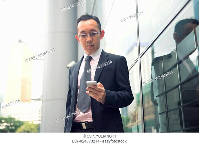 hong kong chinese businessman on a phone in busy central distric