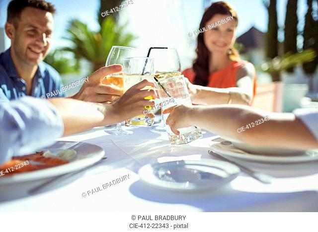 Friends raising toast at table outdoors