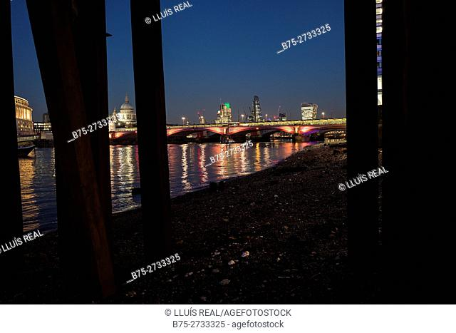 View of the City of London under Lambeth Pier at night, Embankment, River Thames, London, England