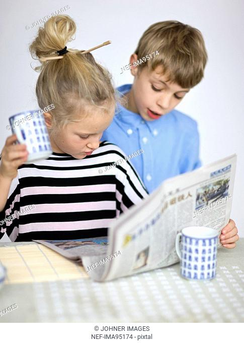 Portrait of boy and girl reading newspaper at table