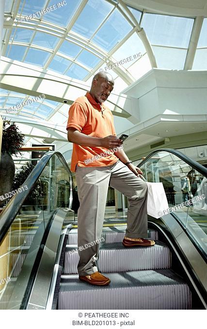 Black man text messaging on mall escalator
