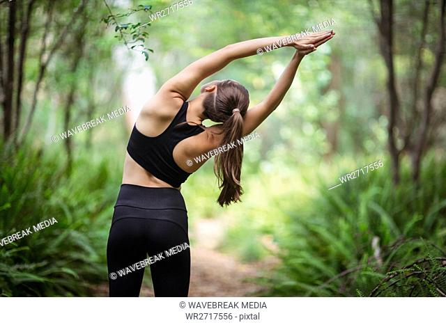Rear view of woman performing stretching exercise
