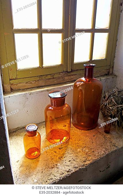 Antique glass bottles on a windowsill of the kitchen pf the Chateau Cassan in Roujan, France