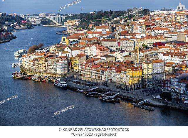 Tourist boats and ships over Douro River in Porto city on Iberian Peninsula, second largest city in Portugal. View with Arrabida Bridge