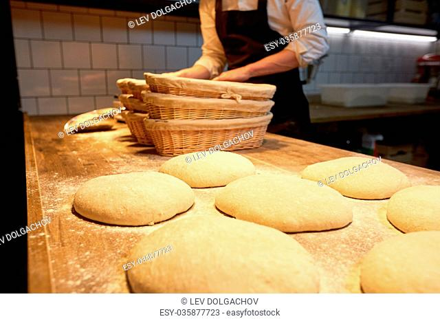 food cooking, baking and people concept - chef or baker preparing baskets while dough rising at bakery kitchen