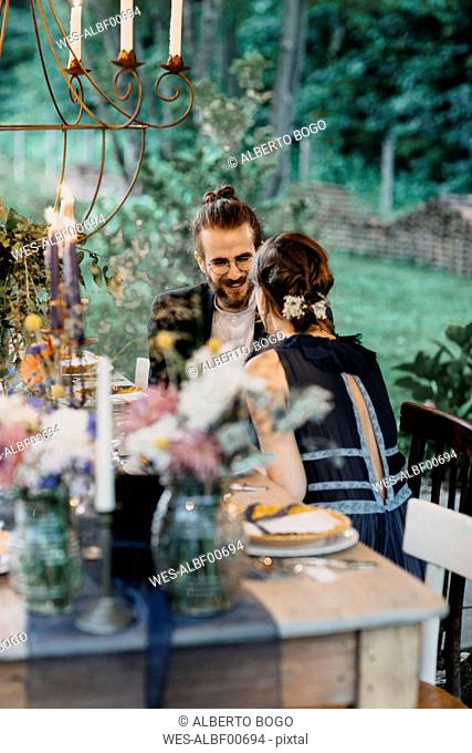 Happy bride and groom sitting at festive laid table outdoors