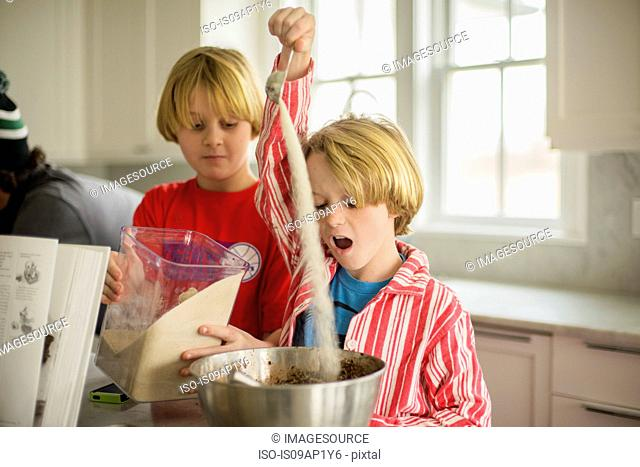 Brothers pouring flour into mixing bowl in kitchen
