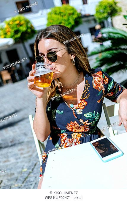 Spain, Cadiz, Vejer de la Frontera, young woman sitting at street cafe drinking glass of beer