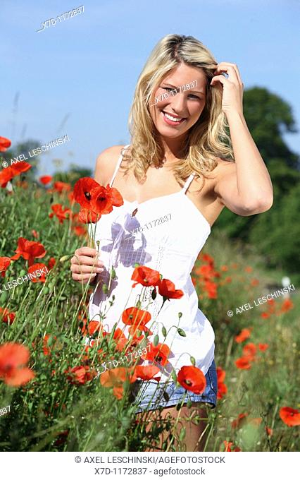 young blond woman  walking through fields holding a bunch of corn poppy