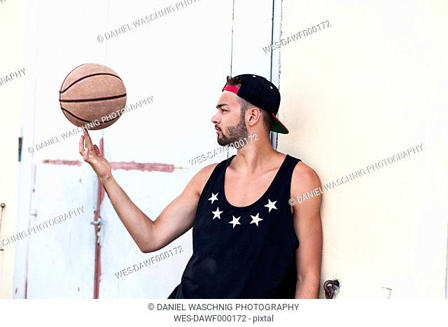 Young man balancing basketball wearing basecap