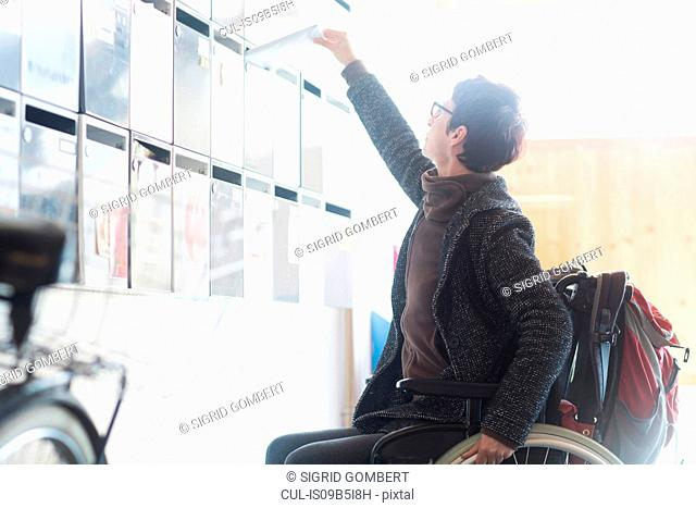 Woman in wheelchair, reaching up, posting mail through letterbox