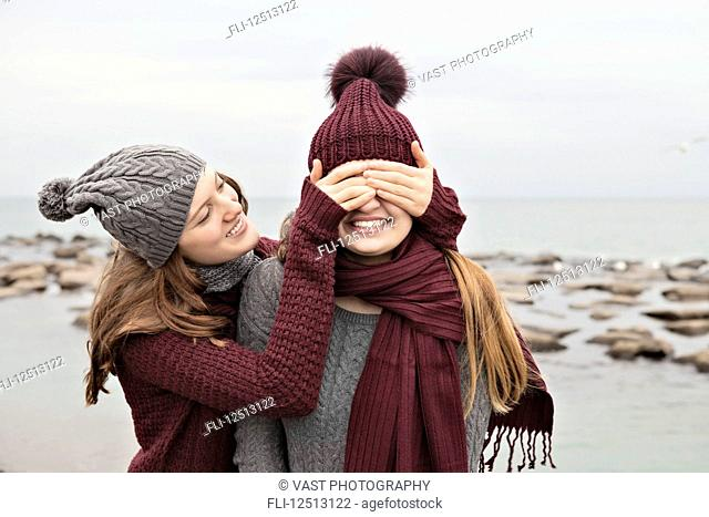 Two friends playing on the beach wearing knit hats and scarves, Woodbine Beach; Toronto, Ontario, Canada