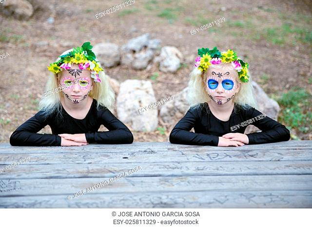 Photo of twin girls with black clothing and sugar skull makeup sitting in front of a table outdoors