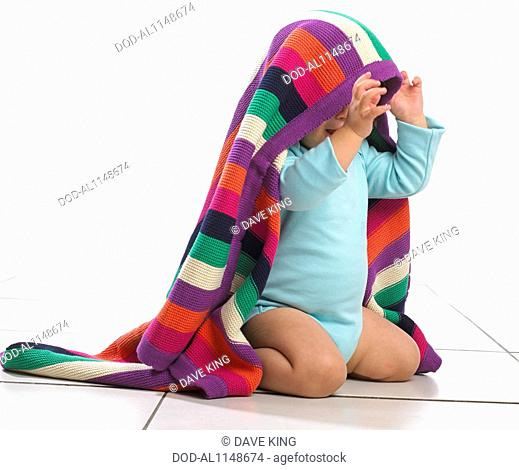 Toddler boy with colourful striped blanket on his head