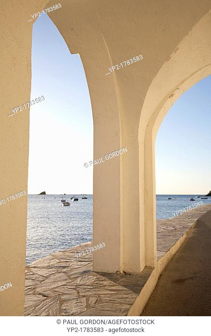 Waterfront arcade along Riba Pitxot - Cadaqués, Catalonia, Spain  Cucurucuc, the small islet Salvador Dalí made famous, stands in the distance