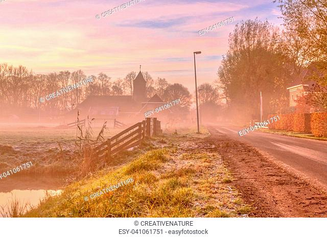 Misty street in dutch rural village on the countryside with church in colorful pink early morning light