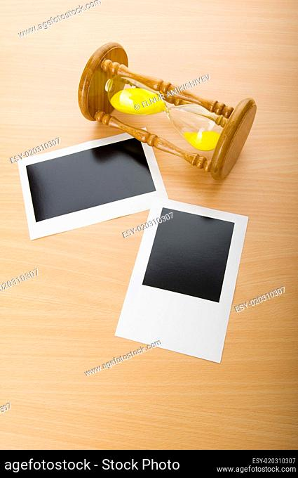 Blank instant photos and hour glass on the wooden table